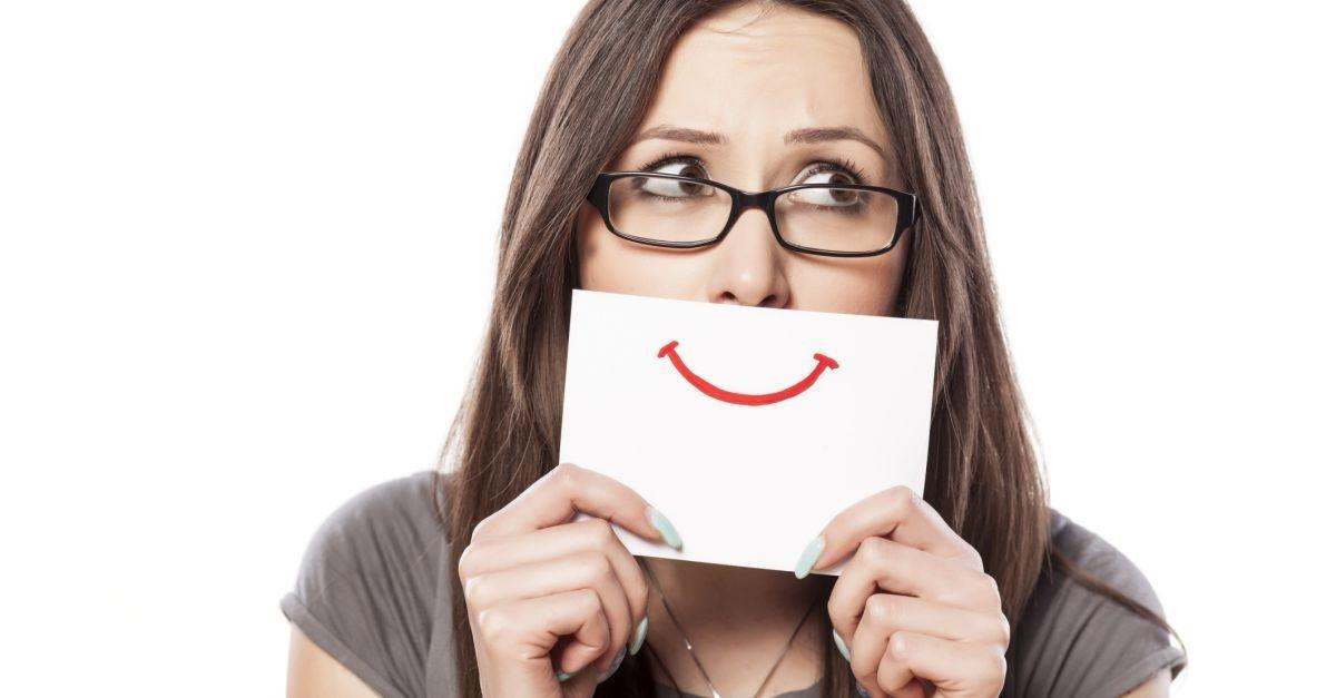 14533-woman-fake-smile-mask-happy-sad-wide.1200w.tn